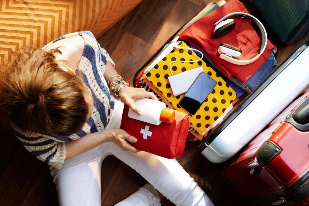 A woman putting medicine in her suitcase