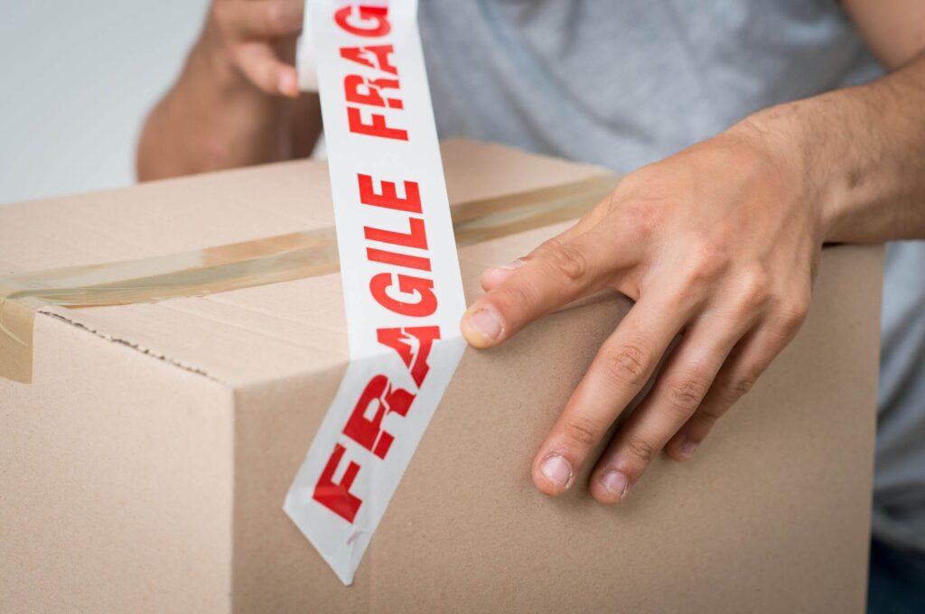 A person taping ''fragile'' on their carton
