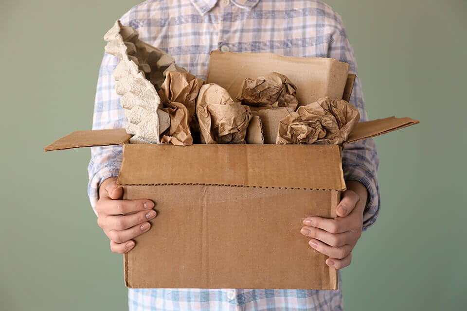 Man holding a box with packing supplies