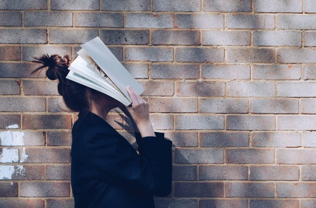 Girl covering her face with a book
