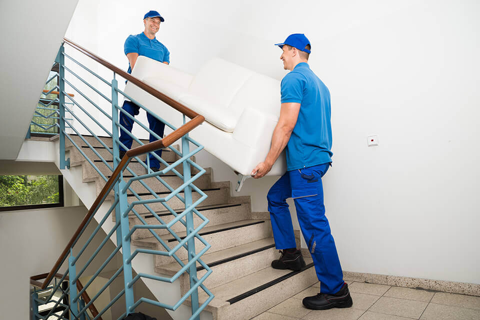Two movers carrying a couch up the stairs